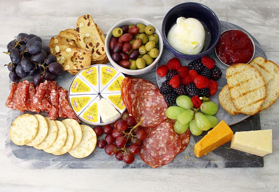 charcuterie board with salami soppresata crackers cheese berries toasts olives and spreads